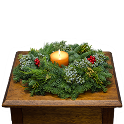 Christmas centerpiece is oval & is decorated with berries and pine cones