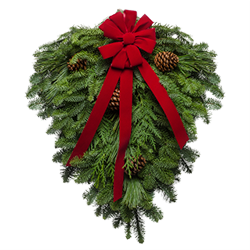 Fresh evergreens gathered together decorated with a red velvet bow