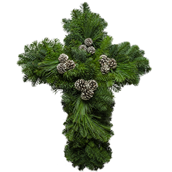 Christian cross made from fresh evergreens and decorated with white painted cones