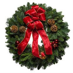 Decorated Christmas wreath topped with a crushed velvet red bow