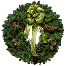 Vintage style Christmas wreaths decorated with a green velvet Victorian bow & painted cones
