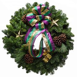 Evergreen Christmas wreath with gold stars, gold drum ornaments, and a bow with Mardi Gras colors
