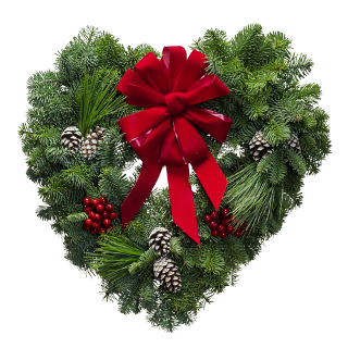 Heart shaped fresh Christmas wreath with a red bow and Christmas descorations