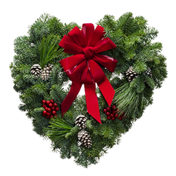 Heart shaped fresh Christmas wreath with red bow and Christmas decorations